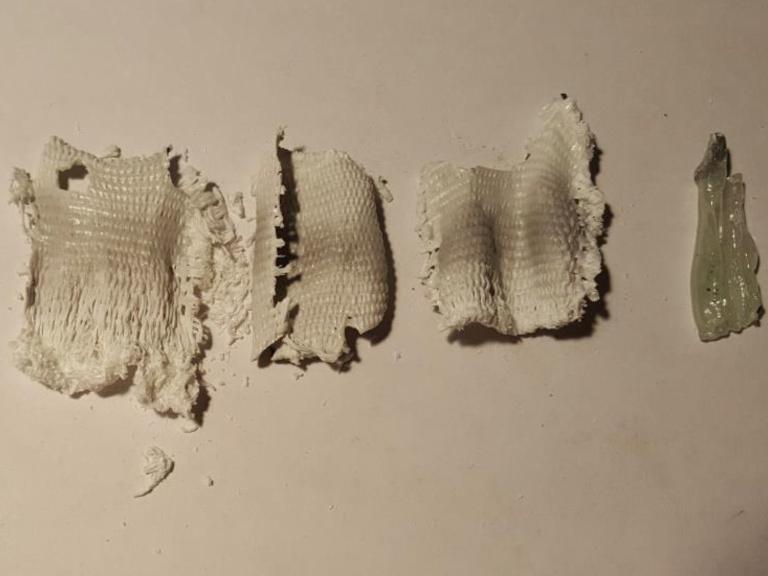 Abbildung 1: Glasfasergewebestücken (5x5cm) veredelt im Vergleich zur geschmolzenen Referenzmatte (rechter Rand) nach einer Temperaturbehandlung bei 950°C